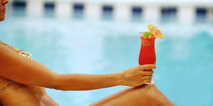 Woman enjoying a cold drink at a Kiva Dunes pool